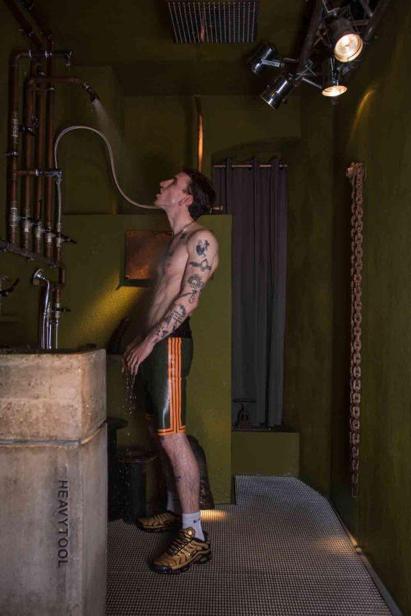 Latex Boxer Hose in olivgrün, eng geschnitten am Bein, mit hohem Bund, orangen Streifen und Logo in weiß orange, Premium Kollektion