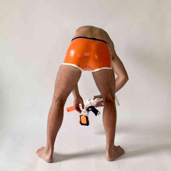 Latex, Rubber Badehose, kurz, eng anliegend in Orange mit blau-weißem Logo. Blauer Bund, weiß gesäumt. Für Herren, Kerle und Jungs