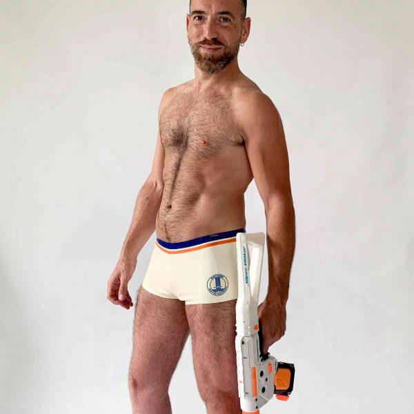 Latex,Rubber knappe Badehose in Weiß mit blau orangem Bund und weiss-blauem Logo für Herren, Kerle und Jungs