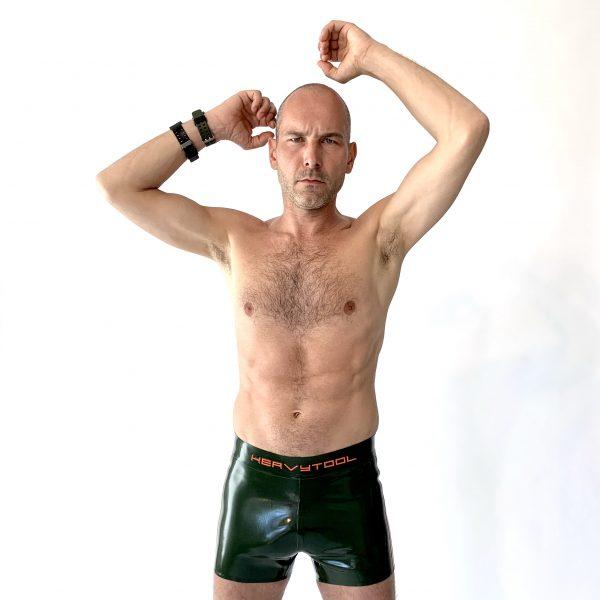 Latex Rubber Hot Pants in olivgrün, eng anliegend mit orange Streifen und Logo für Herren Männer Kerle Jungs