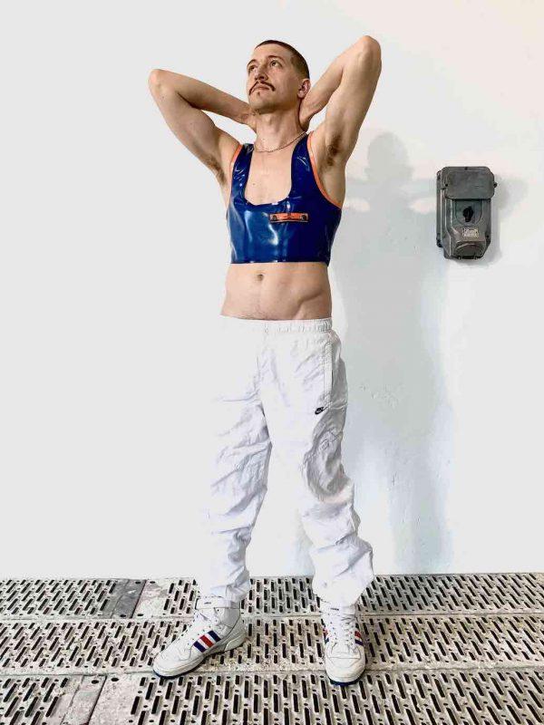 Latex Rubber Crop Top in Transparent Blau mit Logo und orangem Saum. Für Queer Gay Boys, Kerle, Jungs, Männer.