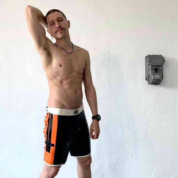 Latex Rubber Schnellficker Hose, maskulin, military mit beidseitiger Knopfleiste. In Schwarz Orange. Für Queer Gay Boys, Kerle, Jungs, Männer.