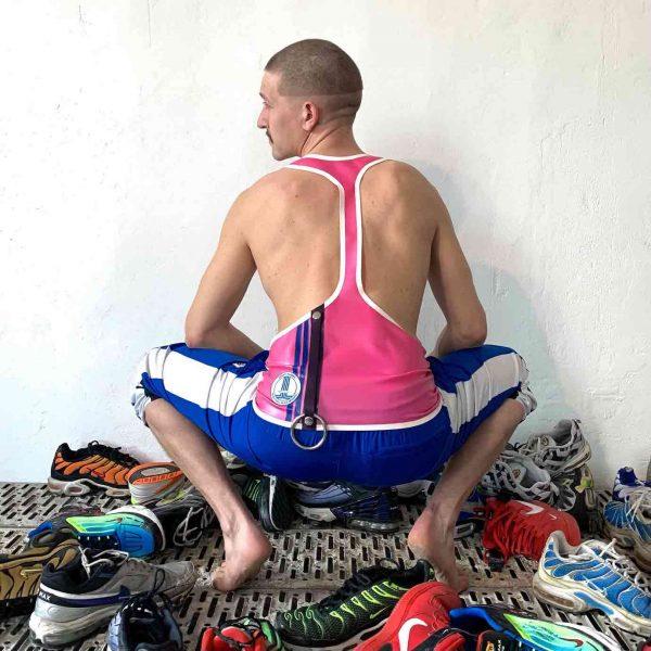 Latex Rubber Tanktop super tief ausgeschnitten in Weiß und Pink mit blauen Bündchen und Logo + Cockring Halter. Für Queer Gay Boys, Kerle, Jungs, Männer.