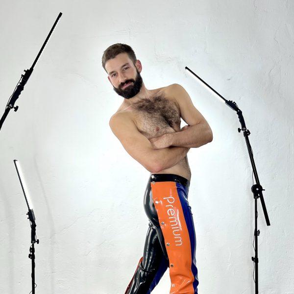 Sportliche Fetisch Latex Rubber  Schnellficker Hose, lang. Premium Kollektion. In schwarz mit orangener Knopfleiste und blauem Frontteil. Logo in silbern. Für Männer, Kerle, Boys und Queers