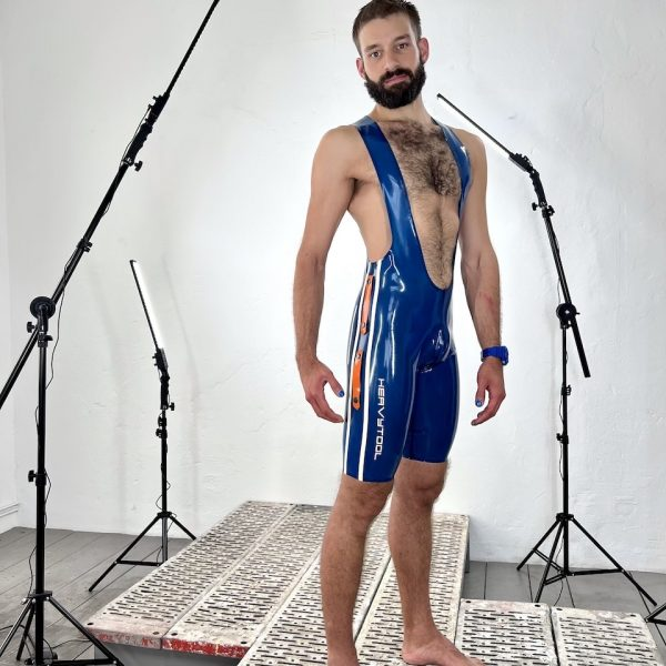 Latex / Rubber Fetisch Wrestlerbody, in transparent blau mit weißen Seitenstrifen, Logo und orangen Design Elementen. Für Männer, Kerle Boys und Queers